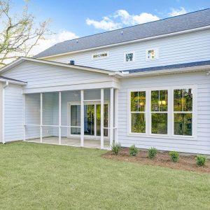 Coastal home with screen porch backyard
